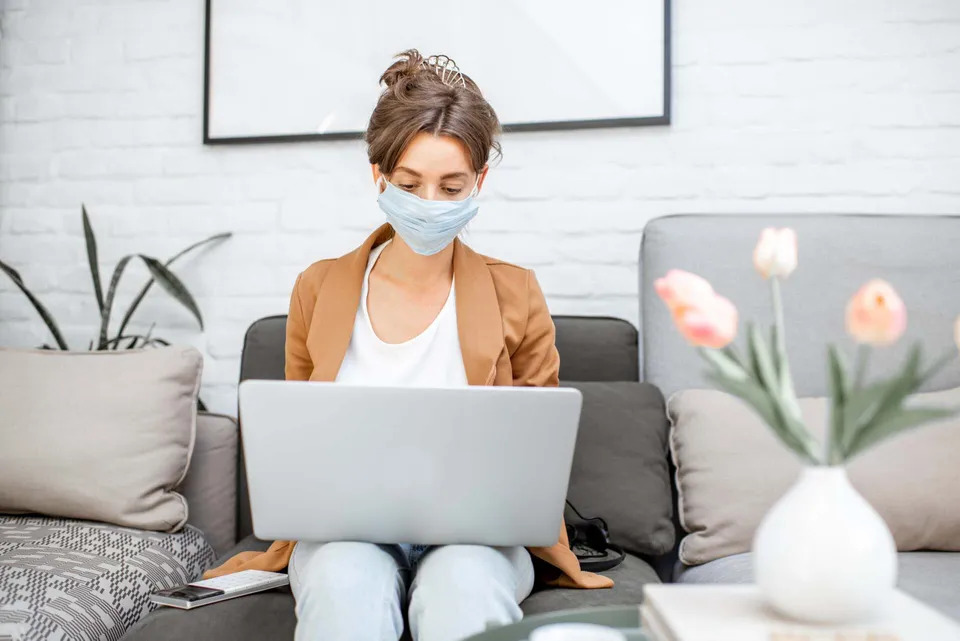 woman-in-medical-mask-working-from-home-B49RM8X-min-960w